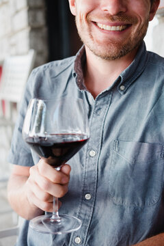 Man holds red wine glass and smiles towards viewer.