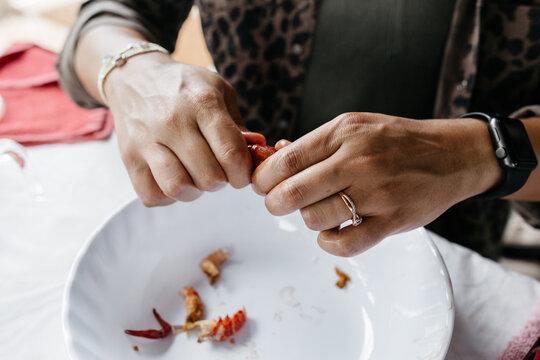 A person peeling and eating Crawfish / Crayfish