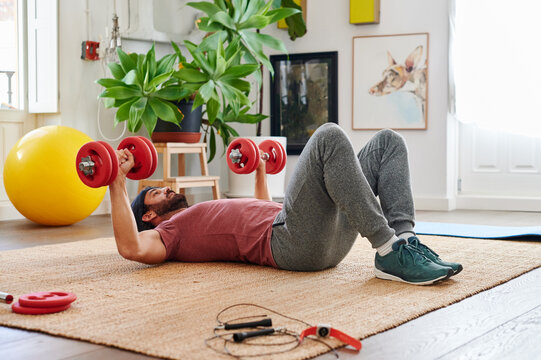 Fit man lifting weights on his living room floor