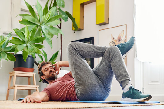 Fit man doing abdominal exercises at home