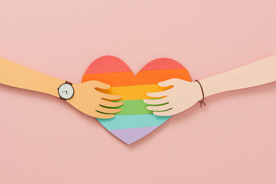 Two human hands reaching to each other over heart shape of the LGBT. Paper cut conceptTwo human hands reaching to each other over heart shape of the LGBT. Paper cut concept