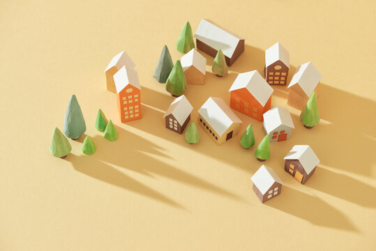 Miniature houses and trees on color background.