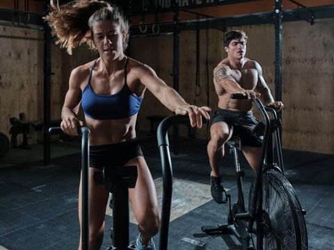 Two athletes with air bikes in the gym