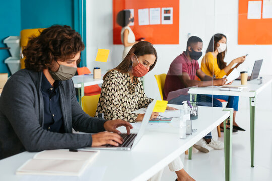 Group of multiracial students in masks working on project in coworking space