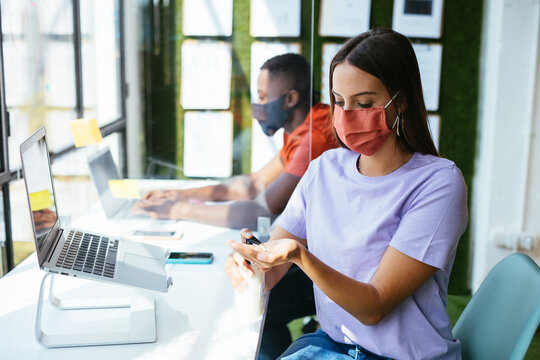 Young woman in mask disinfecting hands in workspace