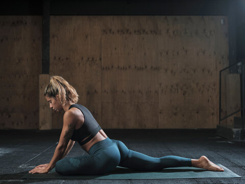 Athlete woman stretching in the fitness gym