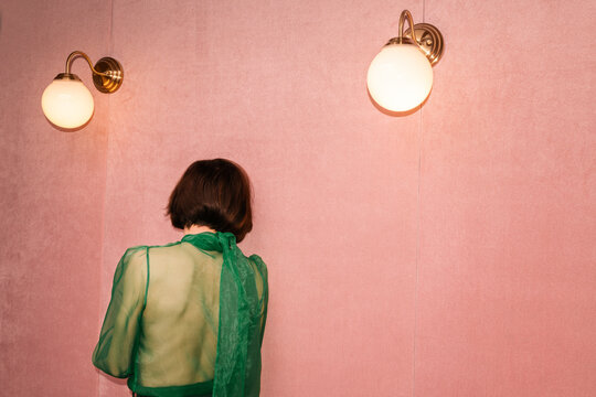 woman with green outfit in a pink room