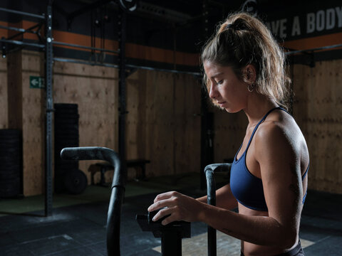 Young athlete woman preparing air bike for workout