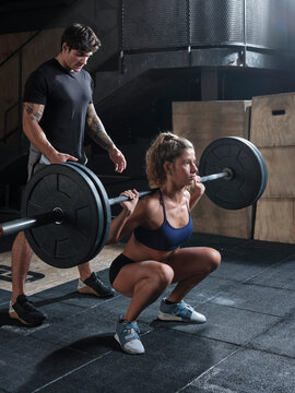 Fitness instructor and athlete woman weightlifting in the gym