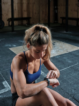 Young woman in a gym checking her fitness tracker