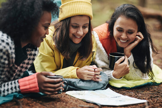 Smiling friends reading a map while camping