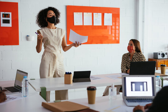 Woman in mask making presentation for colleagues in modern workspace