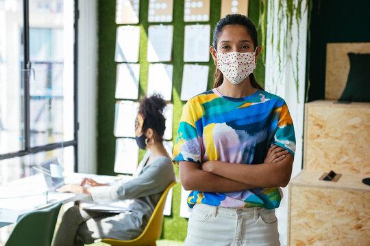 Positive young woman in protective mask standing in creative workplace