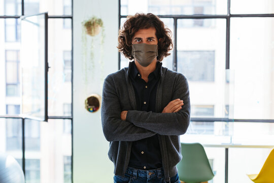 Serious man in protective mask standing near window
