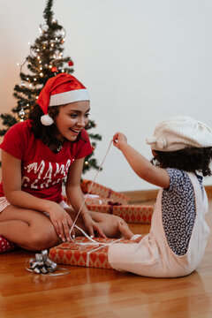 little girl in christmas opening a present gift with her mom