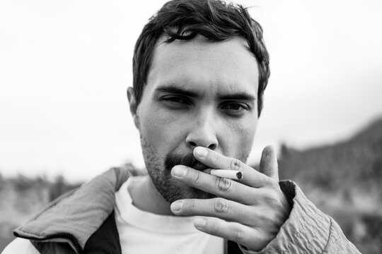 Guy Smoking Cigarette Looking Into The Camera