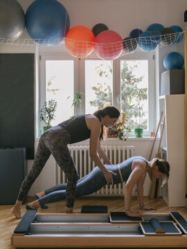 Pilates Coach Working with Woman