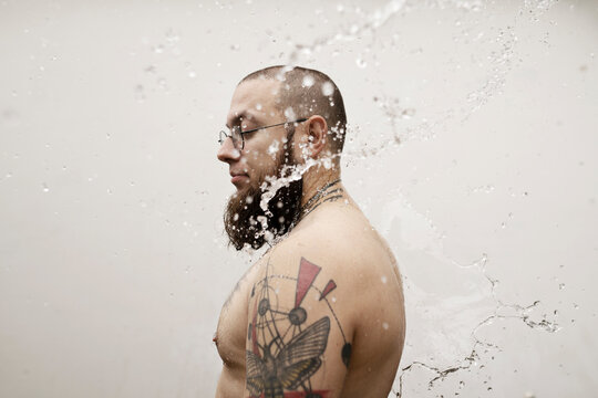 Young man with tattoos stands under a stream of water