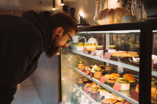 Young man in cafe looking at a showcase with desserts