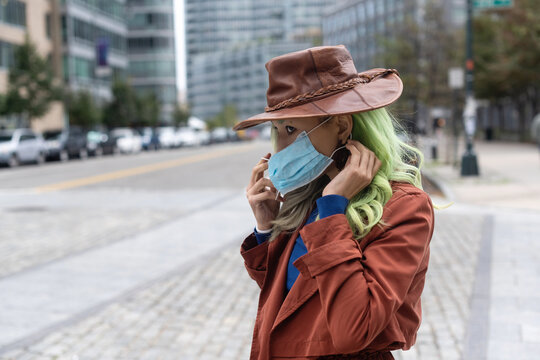 Putting on face mask in street