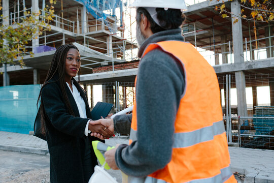 Woman engineer shaking hand with construction foreman in front of construction.