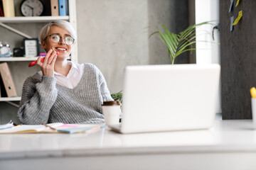 Smiling woman talking on mobile phone while working with laptop