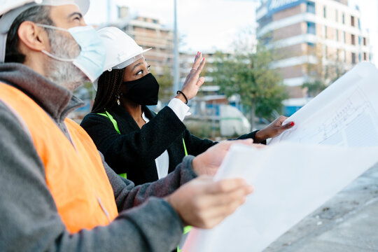 Woman engineer giving instructions to a construction worker.