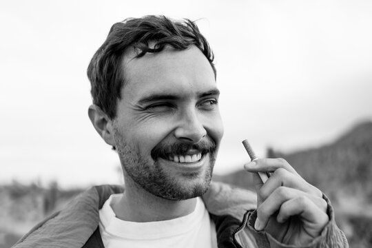 Guy Smoking Cigarette Looking Away From The Camera