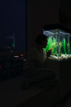 A woman next to a home aquarium.