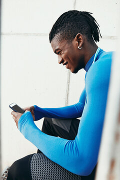 Fit man smiling while texting on his phone