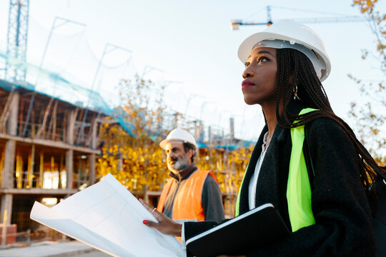 Woman engineer supervising the development of a building in construction checking the plans.