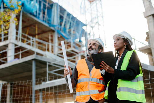 Woman engineer supervising construction of building with construction worker checking her tablet device