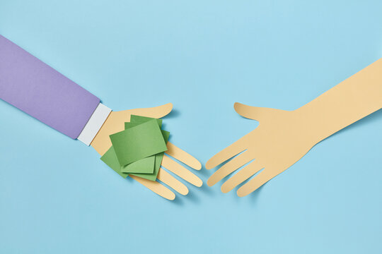 Two papercraft hands with green paper sheets on one.