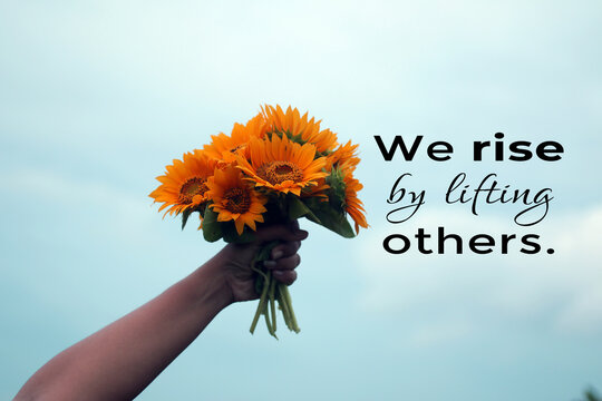 Inspirational quote - We rise by lifting others. Young woman showing bouquet of sun flowers in hand against blue sky background. Positive motivational words concept with sunflowers.