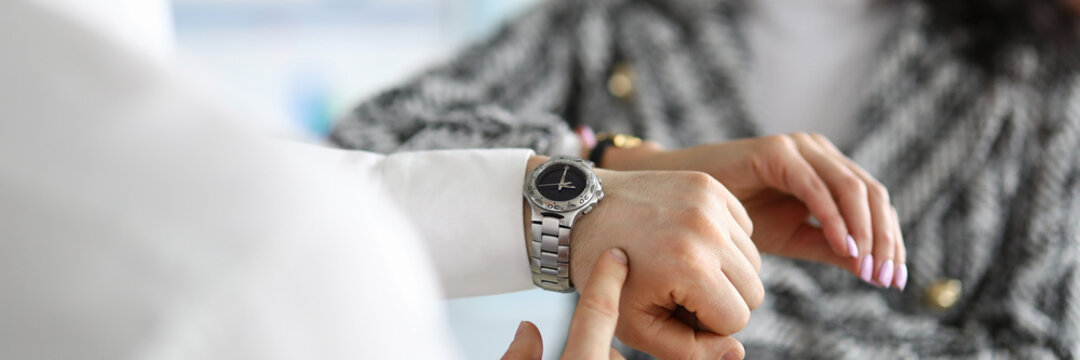 Man and woman check time on clock and arrange business meeting.
