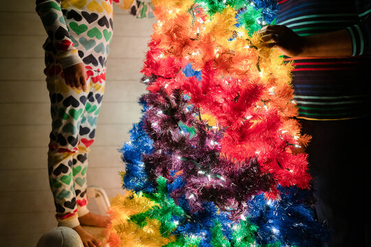 Faceless image of child and adult by rainbow Christmas tree