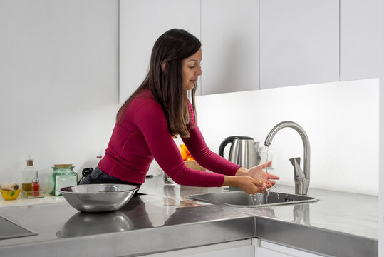 Woman washing her hands on the kitchen