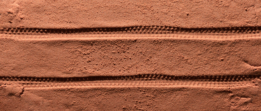 Tyre pattern on the reddish-orange sandy surface with copy space. Imitation of the traces of the rover on the planet Mars. Top view, banner