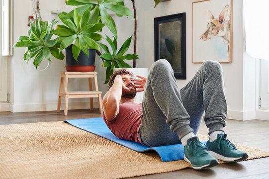Man doing sit-ups at home