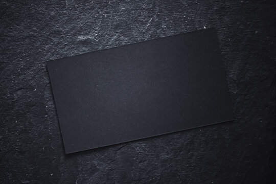Black business card on dark stone flatlay background and sunlight shadows, luxury branding flat lay and brand identity design for mockups