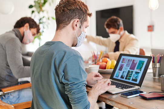 Designer in a face mask using a laptop