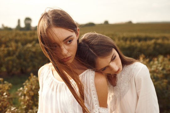 Fashion portrait of two young women models in vintage boho clothes posing among a rural landscape.