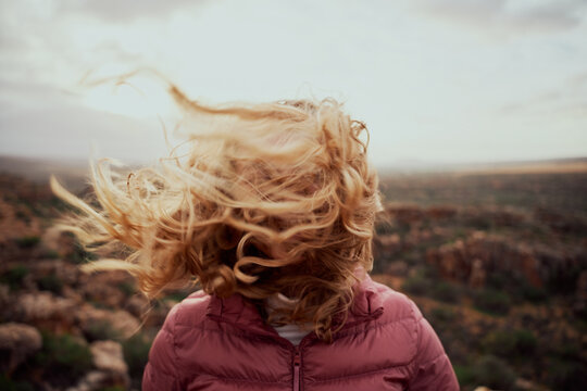 Closeup of young woman face covered with flying hair in windy day standing at mountain