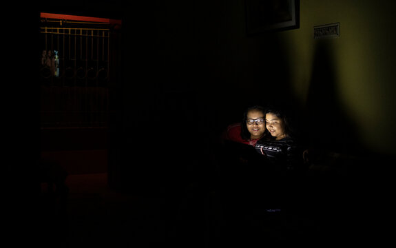 Sisters watching movie in a tablet/laptop inside house at night