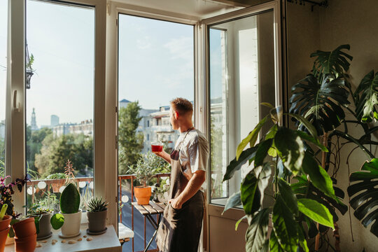 A man on a balcony among green indoor plants.