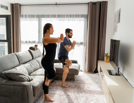 Young couple at home doing yoga balancing pose in living room in front of TV watching online tutorial