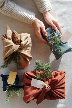 Woman holding Christmas gifts in linen cloth