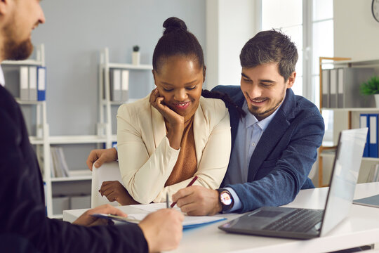 Happy interracial young family couple signing papers after consultation with personal financial advisor about health insurance, budget planning, loan mortgage agreement, real estate sale purchase deal