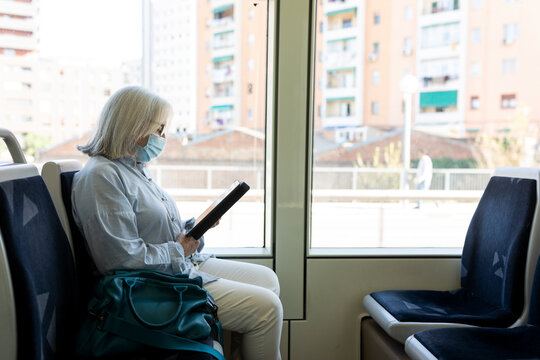 Mature grey hair woman sitting on bus reading a book from a tablet
