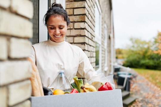 Woman standing with groceries outside
